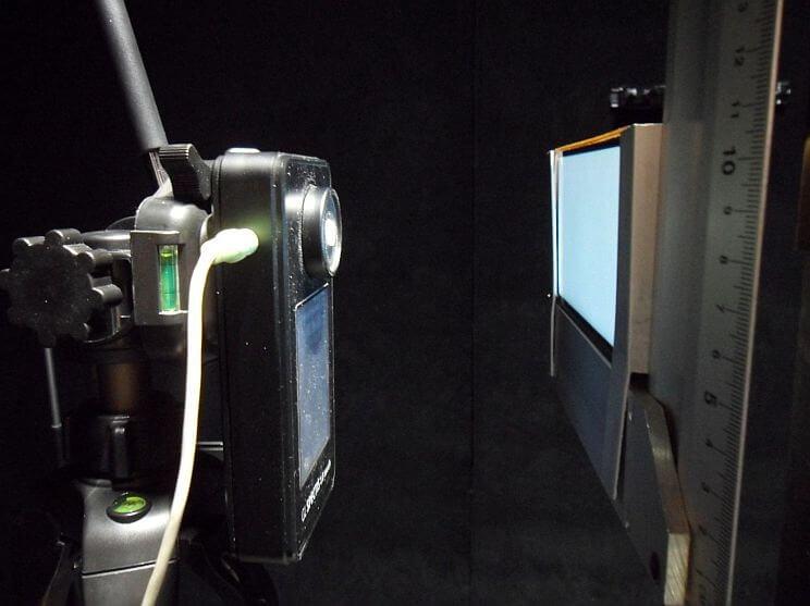 Widok układu pomiarowego (spektrometr wraz z telefonem oraz wyświetlanym białym tłem JPG)